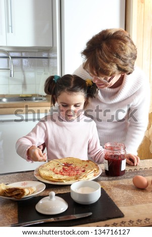 Woman and child making pancakes - stock photo