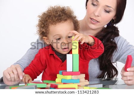 Woman and child playing with building blocks - stock photo