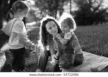 Woman and children having picnic in park - black and white, selective focus on baby - stock photo