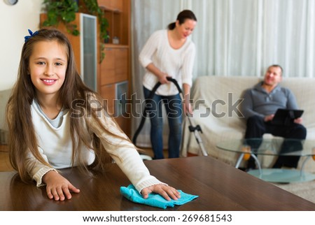 Woman and cute girl doing general cleaning, man having rest - stock photo