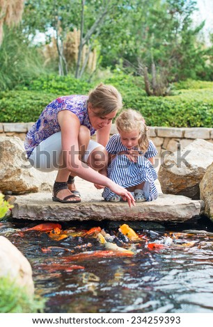 Woman and daughter feeding fishes in pond. - stock photo