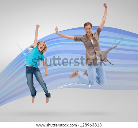 Woman and daughter jumping with clothes turning to paint splatters on blue wave background - stock photo