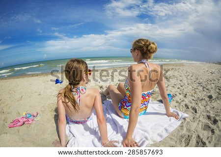 Woman and daughter relaxing on a beautiful beach together on vacation - stock photo