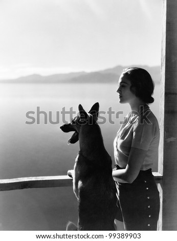 Woman and dog looking out over water - stock photo