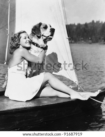 Woman and dog on sailboat - stock photo
