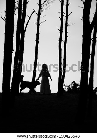 woman and dog silhouettes between trees - stock photo