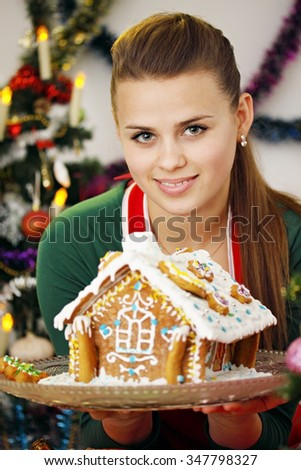woman and gingerbread house. The woman is holding a Christmas dessert - stock photo
