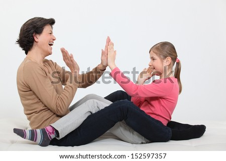 Woman and girl clapping hands - stock photo
