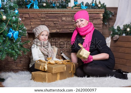 Woman and girl in winter hats and scarfs posing near christmas decorations - stock photo