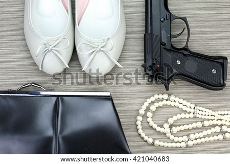 Woman and gun, Pistol and woman accessories, Handgun and accessories, Stylish set for girls. Women accessories, Still life of fashion woman. purse, necklace, women shoes. - stock photo