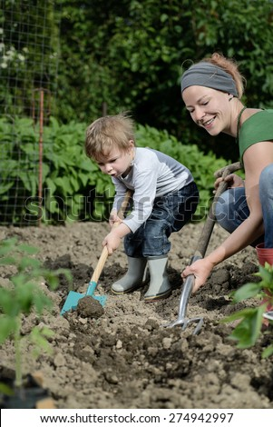 Woman and her child planting cultivating together in garden yard - stock photo