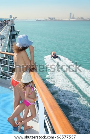 woman and her daughter standing on deck of cruise ship and looking at motor boat. - stock photo