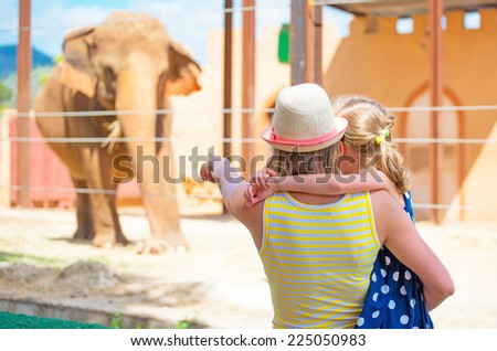 Woman and her daughter visiting zoo. - stock photo