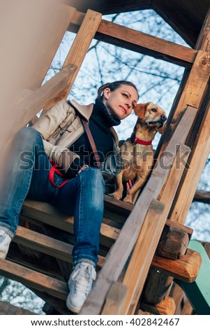 Woman and her dog sitting on wooden stairs looking at far distance - stock photo