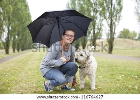 Woman and her dog under an umbrella. She is looking into the camera with a friendly smile. Clothing is casual. - stock photo