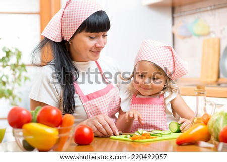 woman and her kid daughter preparing vegetables at kitchen - stock photo