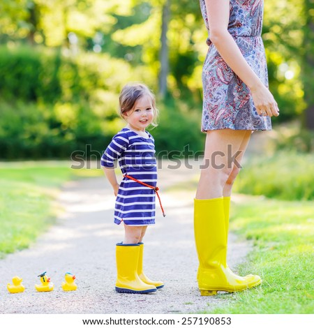 Woman and her little cute kid daughter in yellow rubber boots, family look, playing with duck toys in summer park. Active leisure with kids. - stock photo