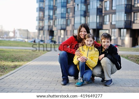 Woman And Her Teenage Children boy and girl outdoor in the city - stock photo