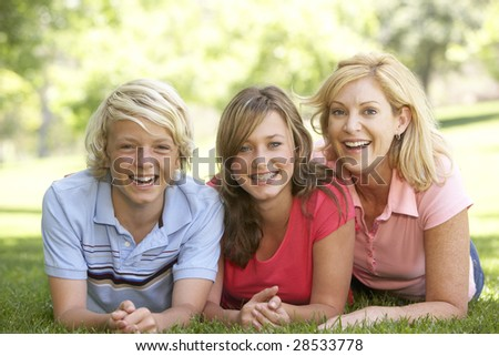 Woman And Her Teenage Children Lying On Grass - stock photo