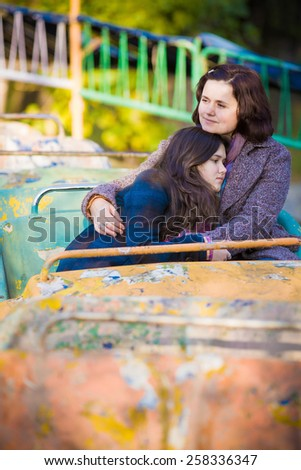 Woman and her teenage daughter embracing and sitting on an old carrousel in a park. - stock photo