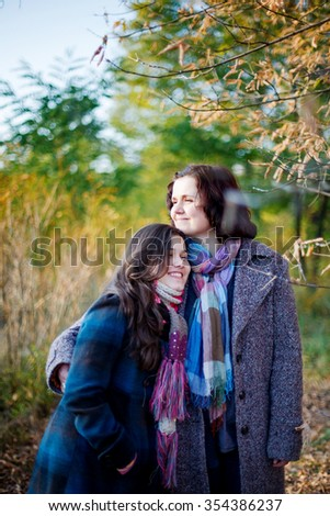 Woman and her teenage daughter in a park. - stock photo
