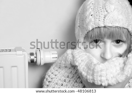 Woman and home heater, cold winter at home - stock photo