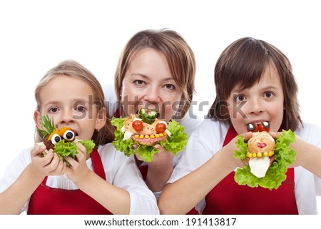 Woman and kids taking a bite from healthy and creative creature sandwiches - closeup - stock photo