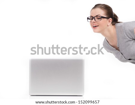 Woman and laptop. Cheerful young women in glasses looking at the computer monitor and smiling while isolated on white - stock photo