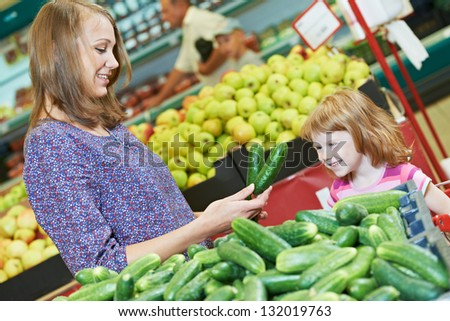 woman and little girl choosing cucumbers during shopping at fruit vegetable supermarket - stock photo