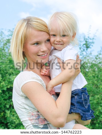 Woman and little girl in the park - stock photo