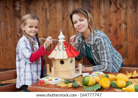 Woman and little girl painting the bird house for winter time - stock photo