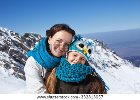 Woman and little girl portrait on a mountain top - enjoying the first snowy days high above - stock photo