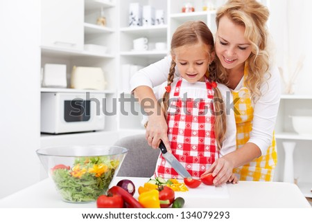 Woman and little girl preparing a vegetables salad in the kitchen - stock photo