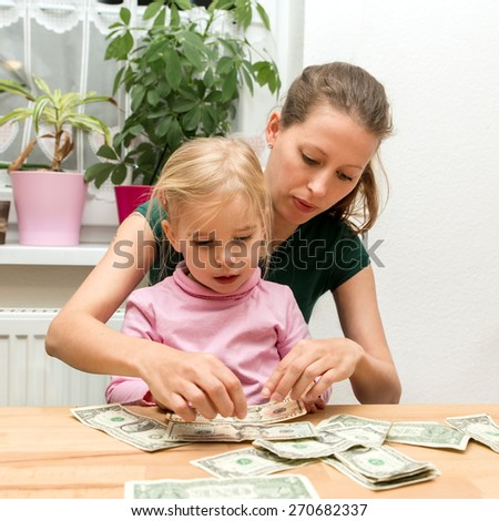 woman and little girl with a lots of dollars - stock photo