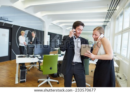 Woman and making making phone calls in office and looking at tablet PC - stock photo