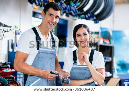 Woman and man as bike mechanics in workshop - stock photo