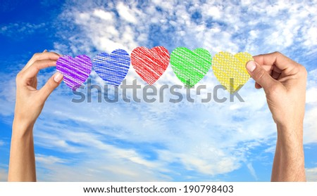 Woman and man hands holding paper hearts over blue sky - stock photo