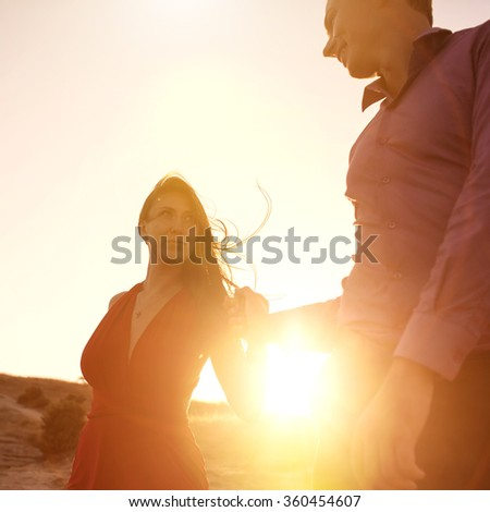 Woman and man holding hands on sunrise - stock photo