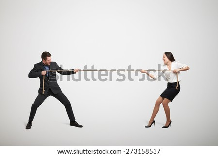 woman and man in formal wear pulling the rope over light grey background - stock photo
