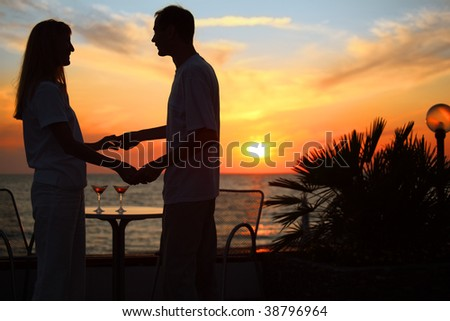 woman and man keep for hands against sunset on sea - stock photo
