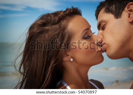 Woman and man kissing at a beach - stock photo