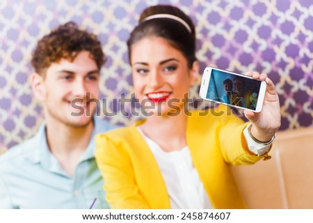 Woman and man sitting at cafe, taking a selfie - stock photo