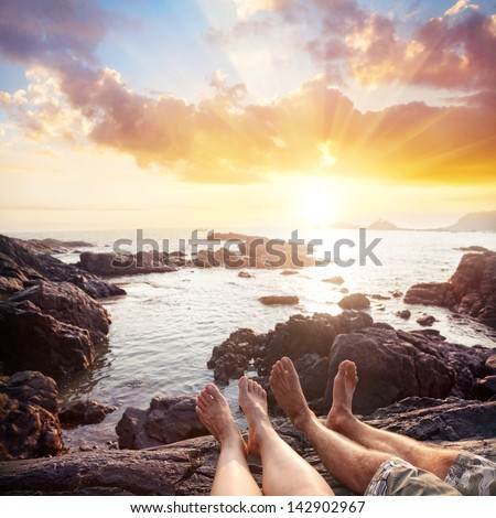 Woman and man sitting on the rocks near the ocean at cloudy sunset sky in Gokarna, Karnataka, India - stock photo