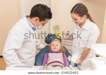 woman and man standing in dental office. dental office and little girl patient sitting in chair - stock photo
