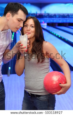 Woman and man together drink milk cocktail from one glass in bowling; woman holds red ball; focus on woman - stock photo