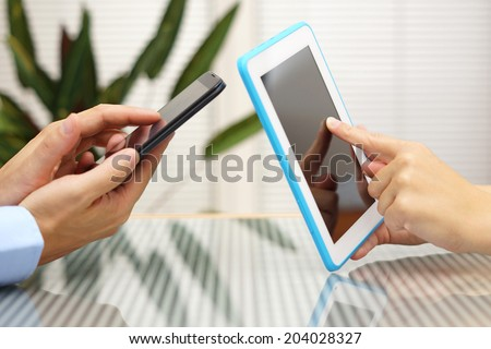 woman and man transferring application from smart mobile phone to tablet pc - stock photo