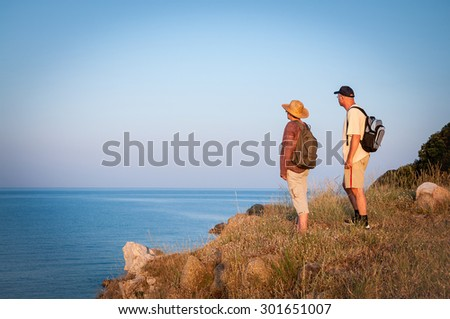 Woman and man with backpacks standing on the top of the mountain in the sunset and enjoying the sea view - stock photo
