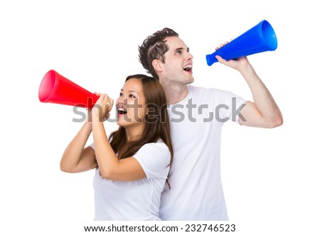 Woman and man yell with megaphone - stock photo