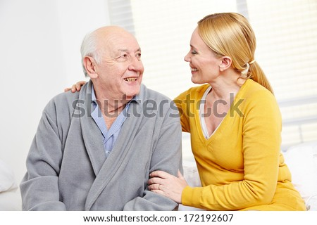 Woman and old senior man in retirement home smiling at each other - stock photo