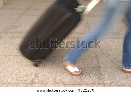 Woman and suitcase. Note that the picture is in motion blur. - stock photo